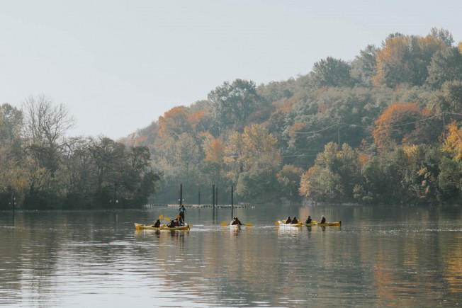 Volunteers on kayaks work on water cleanup.